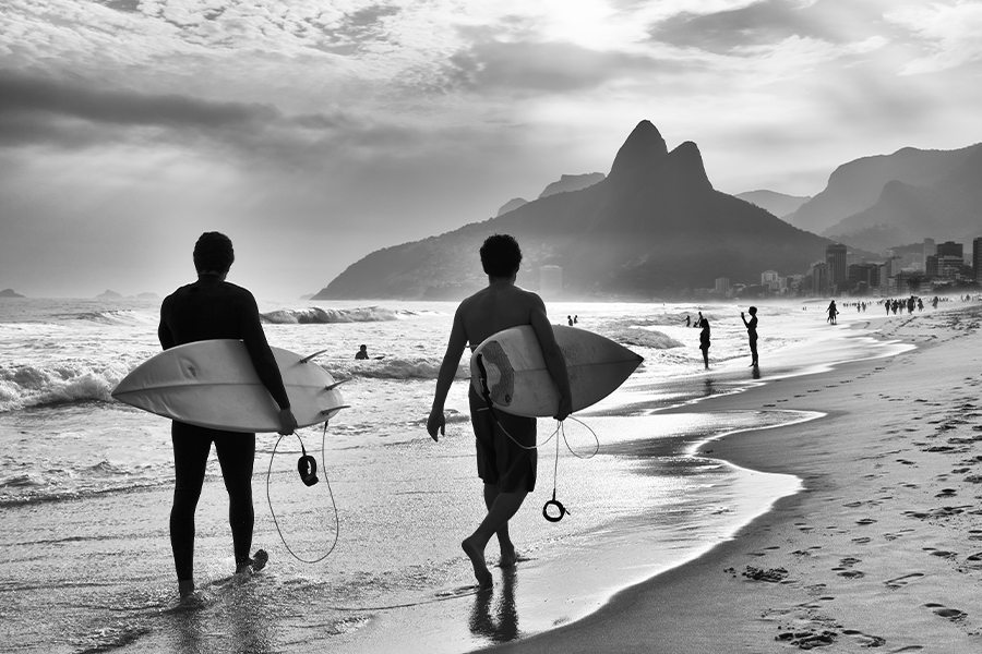 Blog - Surfers Walking on the Beach with City in the Background in Black and White